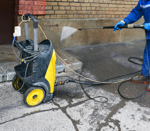 Yellow power washing machine with wand connected spraying water onto wall.